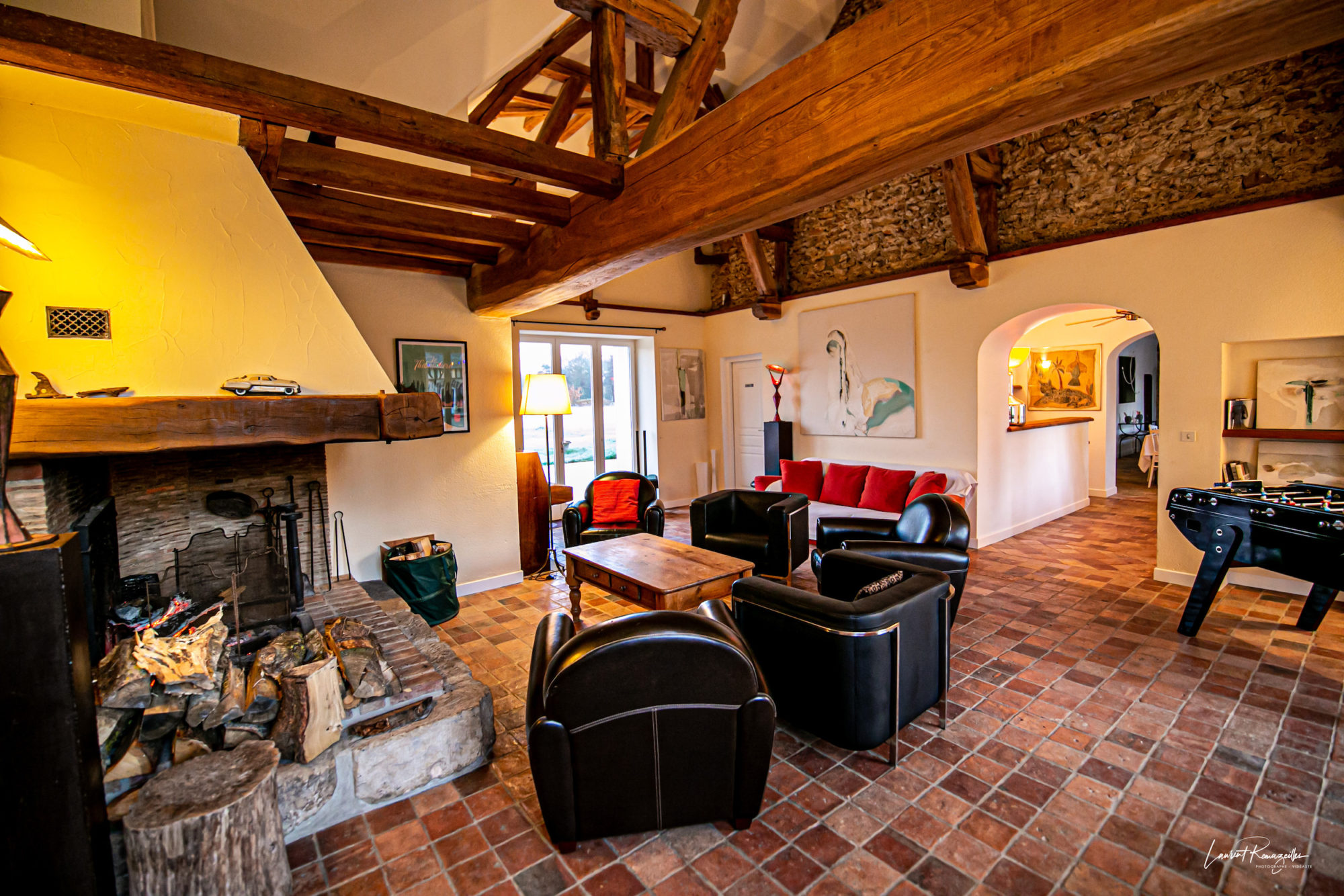 Salon espace détente baby-foot et cheminée à La Thibaudière par Clapinstant